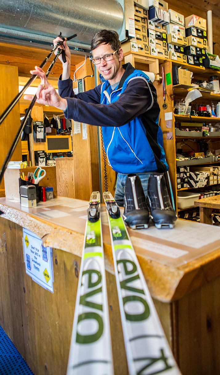 Paul handing over a set of ski poles, skis ready for demonstration